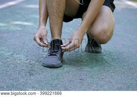 Man Tying Shoelace Before Jogging