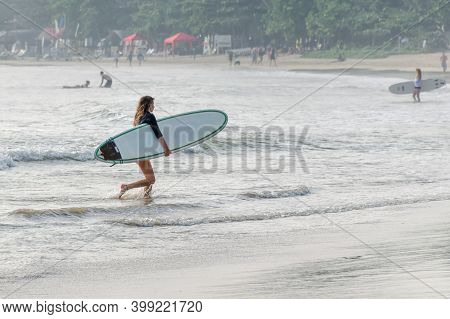 Woman With A Surfboard Comes Out Of The Water. Surf Spot With Foam Waves For Beginners. Sri Lanka, W