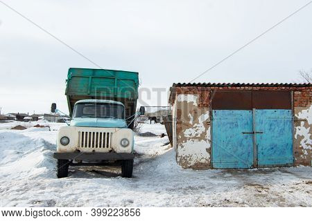 A Heavy Old Blue Dump Truck Is Parked Next To A Building Amid White Snow, Waiting For Loading To Beg