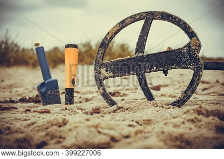 Searching For Treasure. Electronic Metal Detector Coil With Accessories Pinpointer And Shovel On San