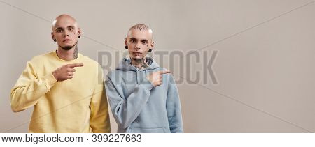 Two Young Twin Brothers In Casual Wear With Tattoos And Piercings Pointing To The Right, Looking At