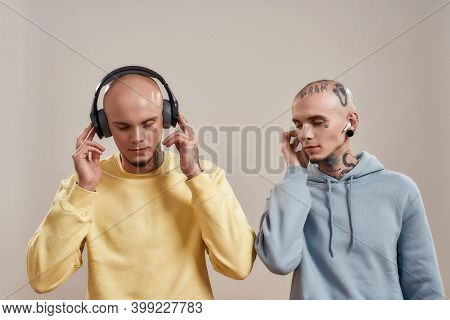 Creative People. Two Young Twin Brothers In Casual Wear With Tattoos And Piercings Listening Music I