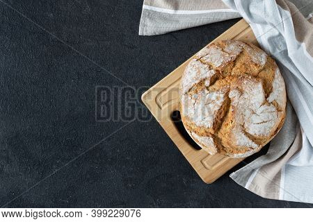 Loaf Of Sourdough Bread With Crispy Crust On Black Background Top View. Healthy Organic Bakery Goods