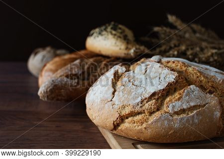 Loaf Of Sourdough Bread With Crispy Crust On Wooden Background. Healthy Organic Bakery Goods.