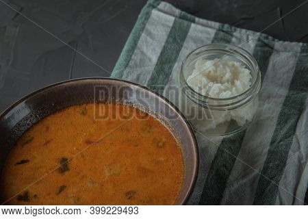 A Plate Of Tom Yam Soup On Towel Strips And Jar Of Rice . Top View