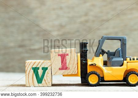 Toy Forklift Hold Letter Block To Complete Word Vi (abbreviation For Value Investor) On Wood Backgro