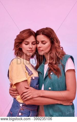 Portrait Of Two Attractive Young Girls, Twin Sisters Holding Each Other, Posing Together With Eyes C