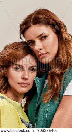 Close Up Portrait Of Two Attractive Young Girls, Twin Sisters Looking At Camera, Posing Together Iso