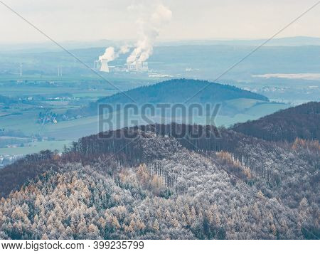 Dark Blue Hills With Hoarfrost Cover And Coal Power Plant Turow In Poland Smoking At Horizon. Misty