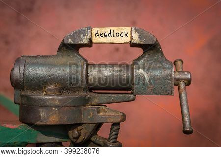 Concept Of Dealing With Problem. Vice Grip Tool Squeezing A Plank With The Word Deadlock