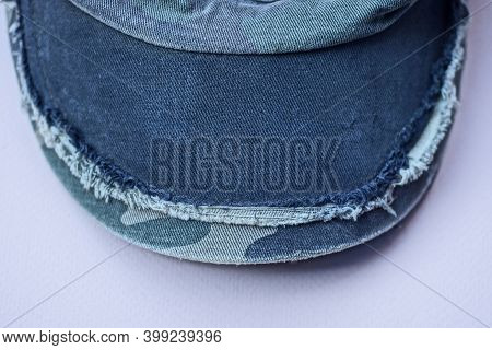 A Black Visor Made Of Shabby Fabric On An Old Cap Lies On A Light Pink Table