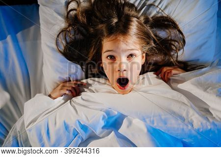 A Frightened Girl In Bed In Her Room, Sees A Nightmare. Childs Fear