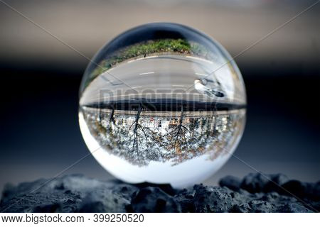 A Riverside Highway View Through A Lens Ball. Glass Ball With Inverted View.