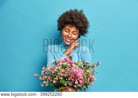 Portrait Of Gentle Dark Skinned Woman Touches Jawline Gently Closes Eyes And Smiles Pleasantly Holds