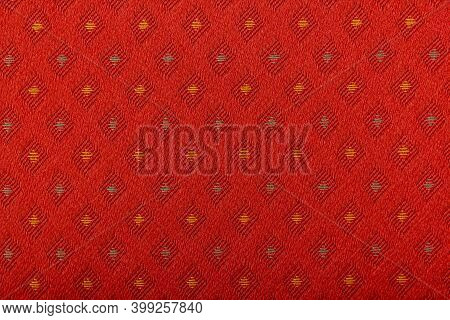 Red Fabric With Yellow Lozenges As The Background Texture. Close-up Long And Wide Texture Of Natural