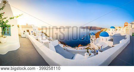 Traditional Greek Village Oia Of Santorini, With Blue Domes Against Aegan Sea And Caldera, Greece, W