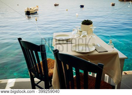 Relaxing Chairs And Dinner Table With View Of Caldera, Santorini, Greece, Toned