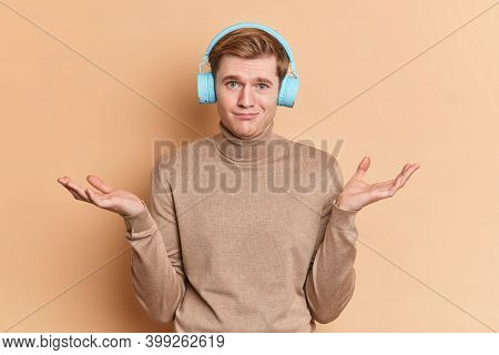 Indecisive Clueless Millennial Guy Spreads Palms And Hesitates About Something Wears Wireless Blue H