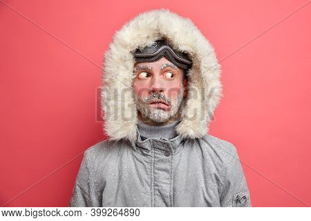Headshot Of Emotive Puzzled Man Purses Lips And Looks Aside Trembles From Low Temperature Needs To W