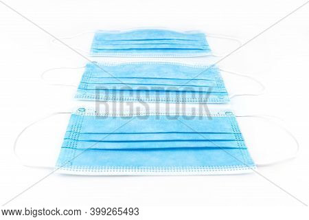Three Blue Surgical Masks For Personal Protection Against The Virus, Isolated On A White Background.