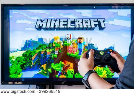 Woman Holding A Xbox Controller And Playing Popular Video Game Minecraft On A Television And Pc