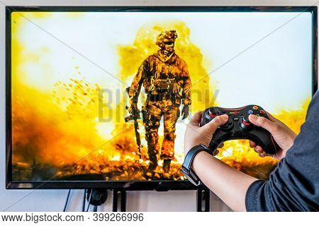 Woman Holding A Generic Controller And Playing Popular Video Game Call Of Duty On A Television And P