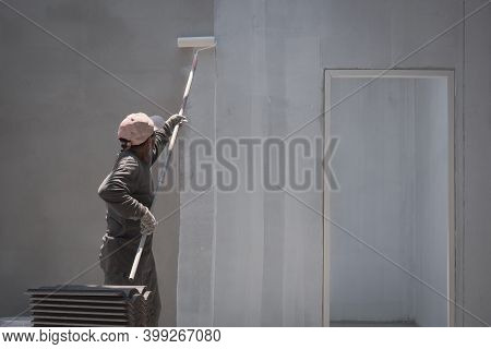 Rear Side View Of Asian Builder Worker Using Long Handle Roller Brush To Applying Primer White Paint