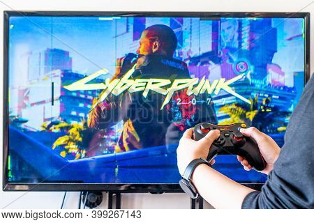 Woman Holding A Red Gear Controller And Playing Popular Video Game Cyberpunk 2077 On A Television An