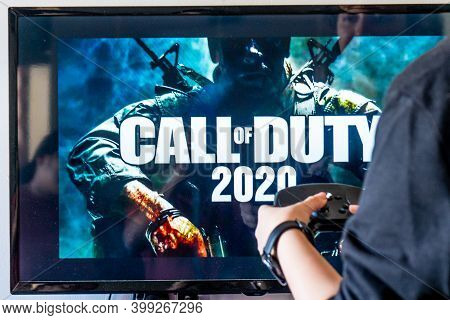 Woman Holding A Steam Controller And Playing Popular Video Game Call Of Duty On A Television And Pc