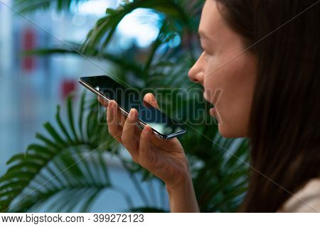 Send A Voice Message Or Communicate With A Digital Voice Assistant. Young Woman Sits At A Table In A