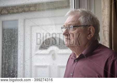 Bored And Fed Up Senior Man Looking Through The Window On A Rainy Miserable Day