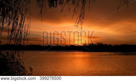 Amazing Sunset Or Sunrise In Front Of The Water. Beautiful Landscape With A Lake And Dramatic Sky Wi