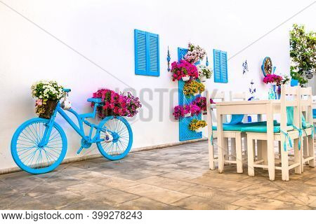 Beautiful street bar (restaurant) decoration with colorful umbrellas, vintage bicycle and flowers