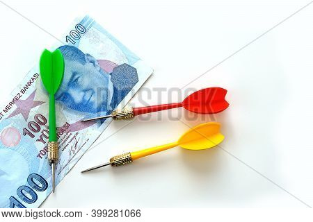 Investing With Yellow, Green And Red Darts And 100 Turkish Lira On A White Background, And Turkish L