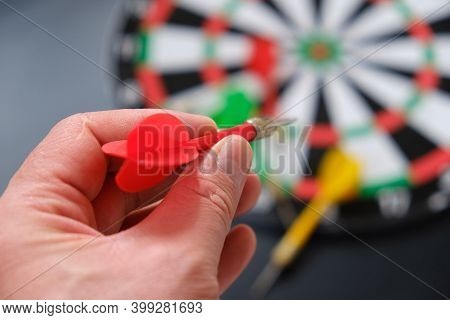 A Hand Throws Darts On A Dartboard, A Hand Holding A Dart, A Colorful Dart And A Dartboard,