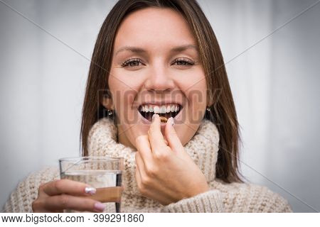 Young Beautiful Smiling Woman Taking Fish Oil Pill. Taking Capsule With Omega 3 Or Vitamin D3. Vitam