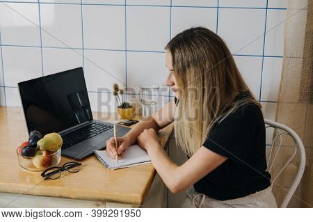 Shopping List, Online Shopping, Save Money. Young Woman Writing Shopping List Sitting Near Laptop At