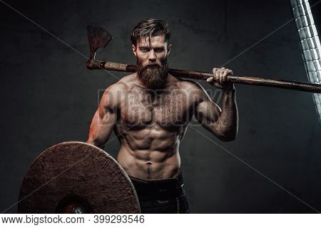 Furious Medieval Nord Warrior With Muscular Build And Naked Torso Posing In Dark Background Holding