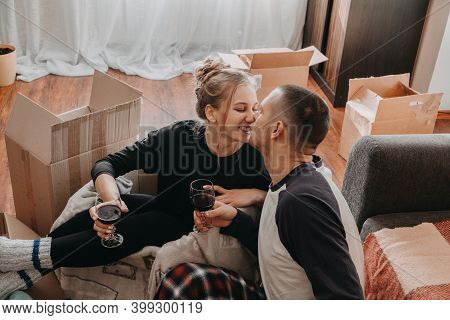 Moving Day, New Home, Valentines Day, Unpacking Boxes, Newlyweds Concept. Couple Celebrating Moving