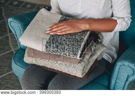 Female Hands Hold A Stack Of Warm Knitted Sweaters