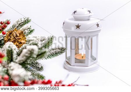 Christmas Decorations On A Light Background And A Christmas Lantern With A Burning Candle Close Up