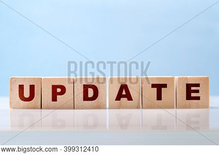 The Word Update Is Written On Wooden Blocks On A Glossy Desktop Surface On A Blue Background