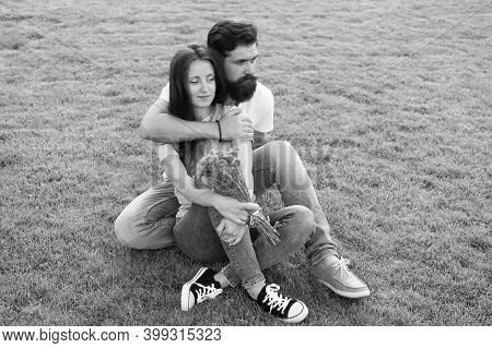 During Outdoor Recreational Activities. Couple In Love Sit On Green Grass Outdoor. Summer Vacation.