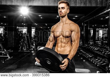 Muscular Sports Guy, Shirtless, Bodybuilder Performs Exercises With Dumbbells In The Gym