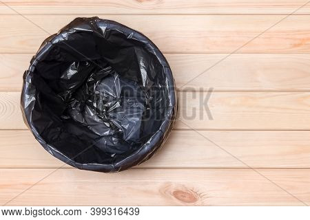 Empty Bin On Wooden Background. Trash Can Top View. Garbage Basket. Rubbish Black Bag In A Trash Can