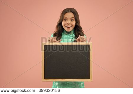 Little Schoolchild Got Blackboard For Lesson. Blackboard For Advertising Text, Copy Space. Happy Gir