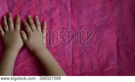 Toddler Hands On Crumpled Pink Paper With Copy Space. Top View Kid Hand Palms On Paper Textured Back