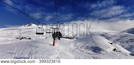 Chair-lift And Off-piste Slope With Trace From Skis And Snowboards In High Winter Mountains. Caucasu