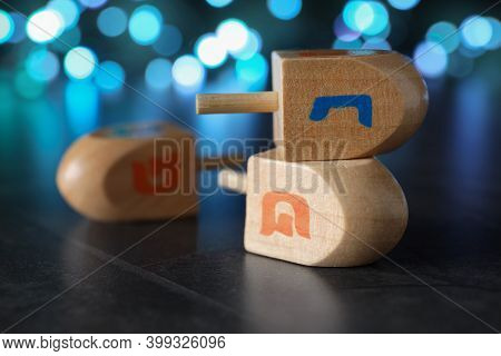 Hanukkah Traditional Dreidels With Letters Nun And Shin Against On Table Blurred Lights, Closeup