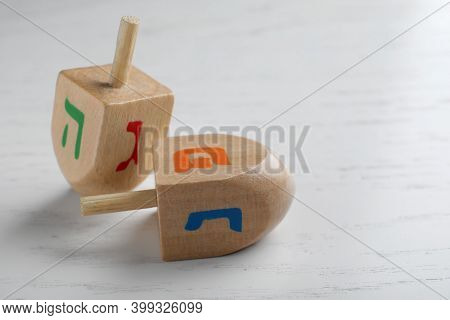 Hanukkah Traditional Dreidels With Letters Hei, Nun, Gimel And Shin On White Wooden Table, Closeup